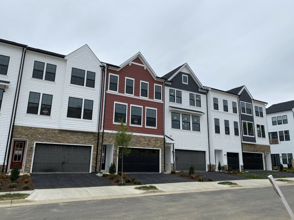 A row of new construction townhomes, each with a little different color and features.