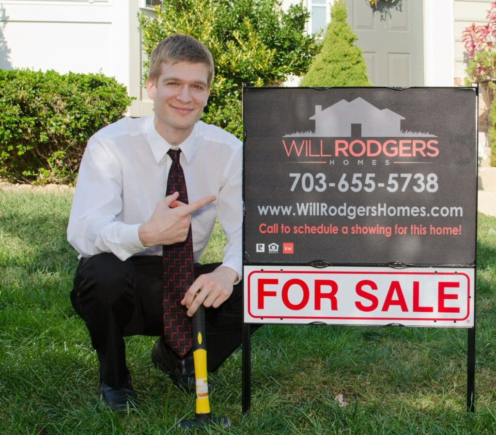 New real estate agent kneels beside real estate sign outside of a home for sale.