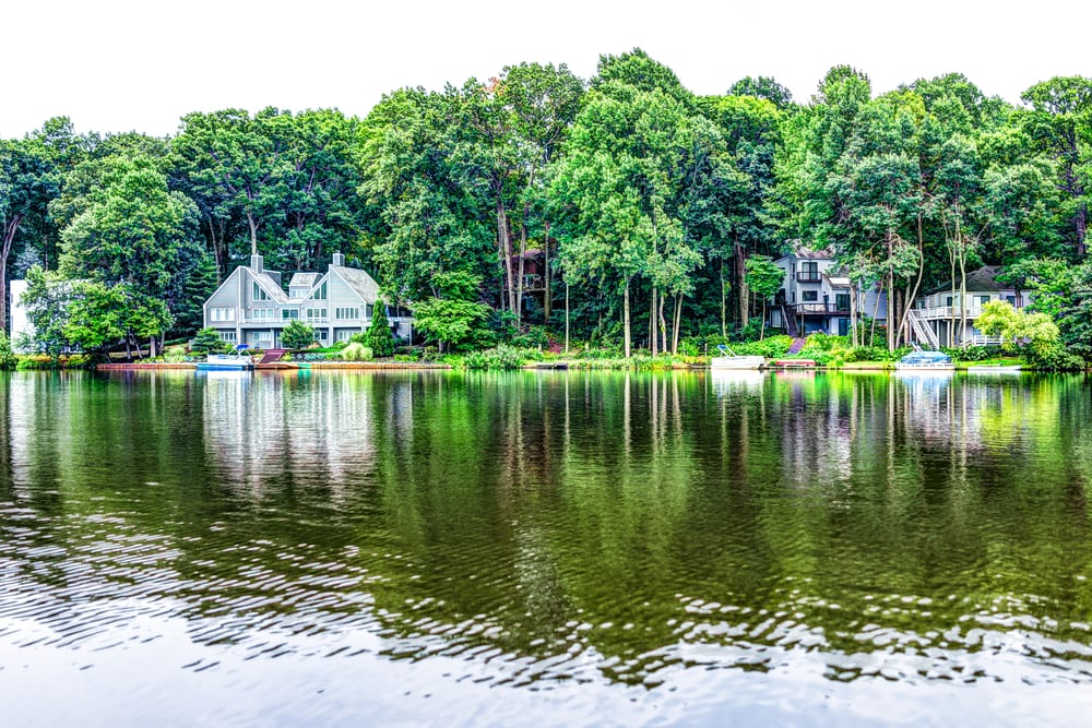A lake with some waterfront homes along the shore. The homes have wooded yards and are located in Reston VA.
