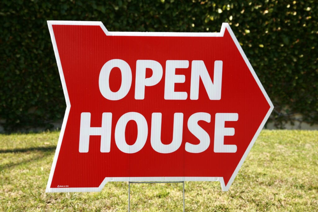 An open house yard sign with an arrow directing people which way to go.