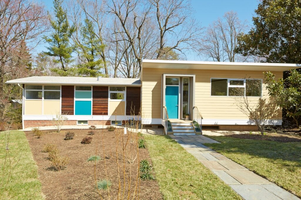 A mid century modern home with a small addition on the side. Light colored siding and bright blue door.
