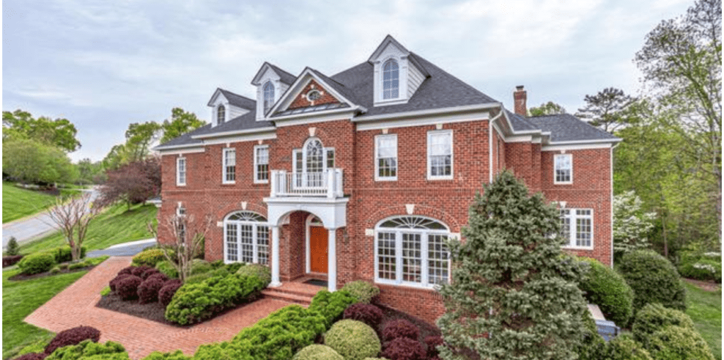 A large brick home with a colonial exterior style. Extensive landscaping out front.