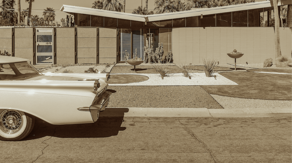 A mid-century modern home with a 1950s sports car parked at the curb.