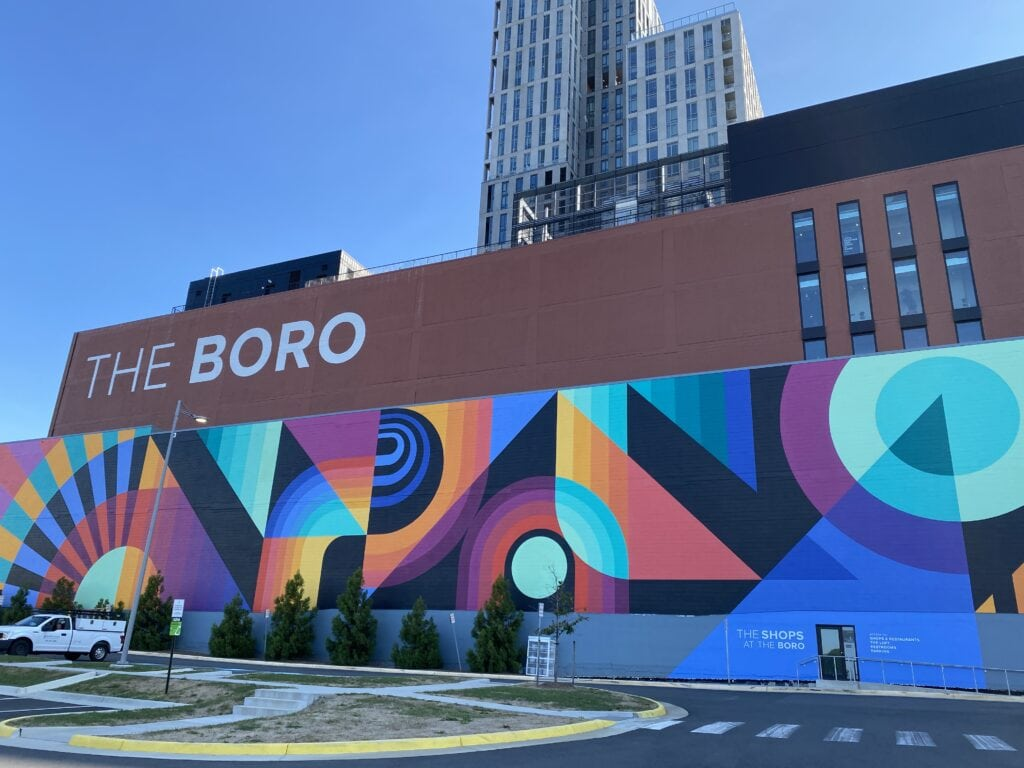 A mural with modern artwork and a sign that states 'The Boro'. Entrance to an urban neighborhood in Northern VA.