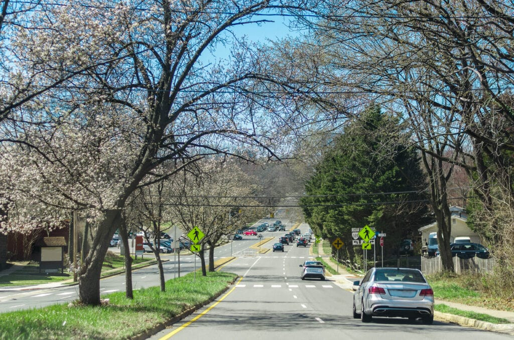 A road leading into McLean VA in the springtime, cars driving along a 4 lane road.