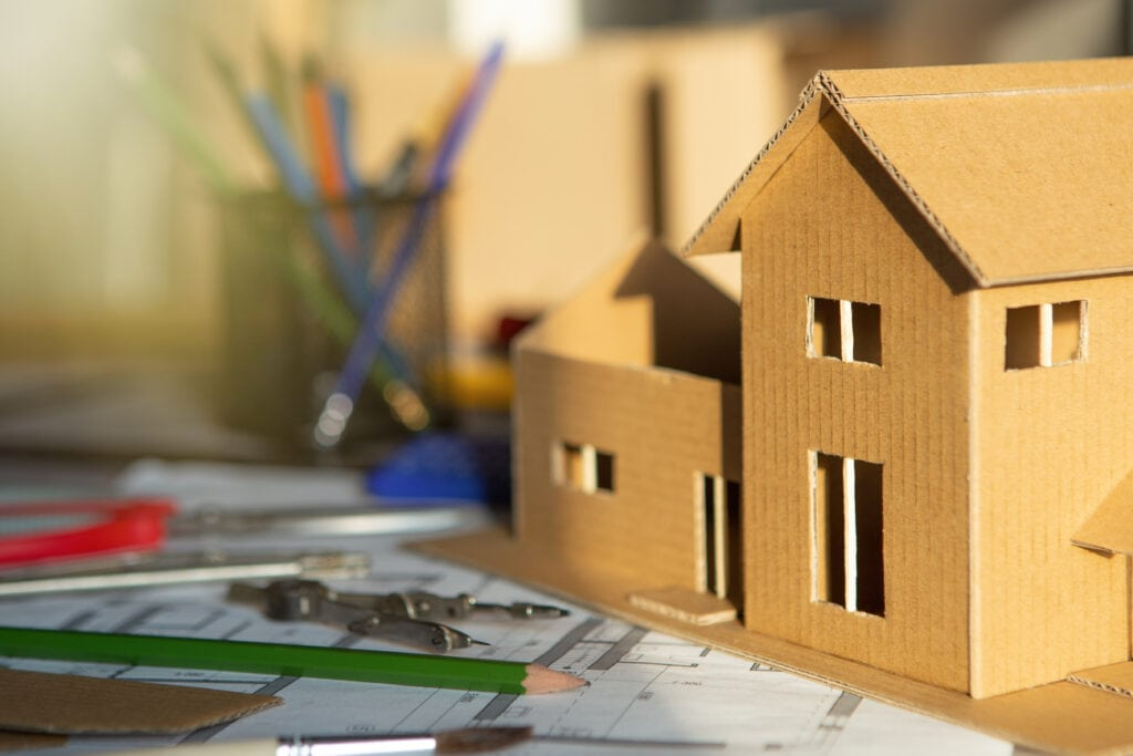 A stock image of a cardboard home with pens in the background.